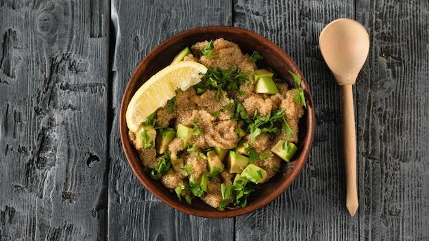 暗い木製のテーブルにアボカド、レモン、パセリのアマランスシードサラダの粘土ボウル