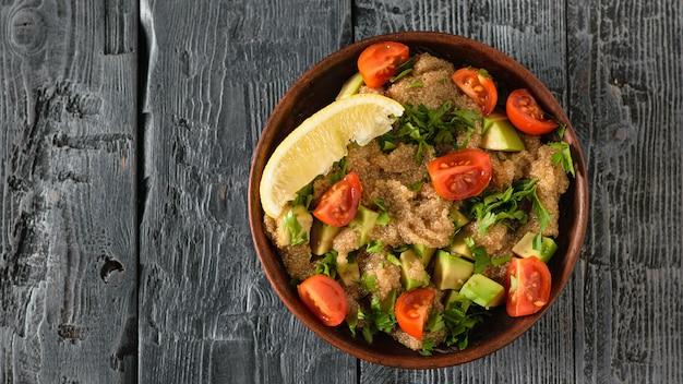 テーブルの上のアボカド、レモン、トマト、パセリのアマランスシードサラダの粘土ボウル。上からの眺め。
