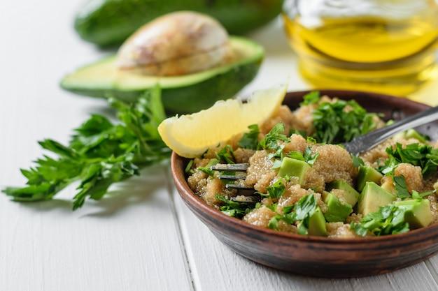 アマランスシードサラダアボカドスライス、レモン、パセリの白い木製のテーブルの上に粘土ボウル。