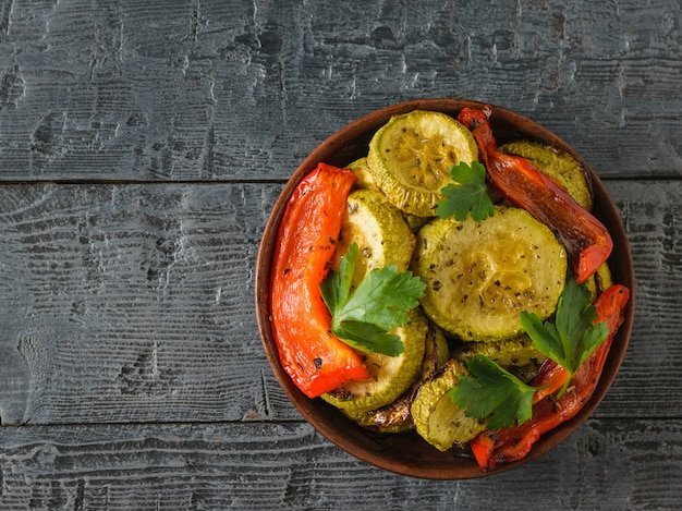 Clay bowl with baked zucchini and red pepper on black wooden table.