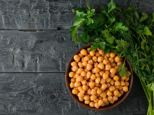 Clay bowl with boiled chickpeas and herbs on a black wooden table