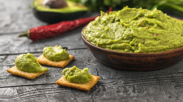 Clay bowl with fresh guacamole, tomatoes, lemon, chips, avocado and garlic on wooden table