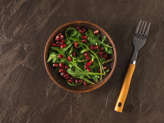 석류 씨앗과 arugula와 돌 테이블에 포크와 점토 그릇. 다이어트 채식 샐러드. 평평하다.