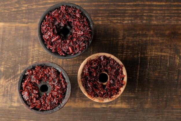 Глиняные чаши для кальяна с табаком на коричневом деревянном столе. аксессуары для кальяна