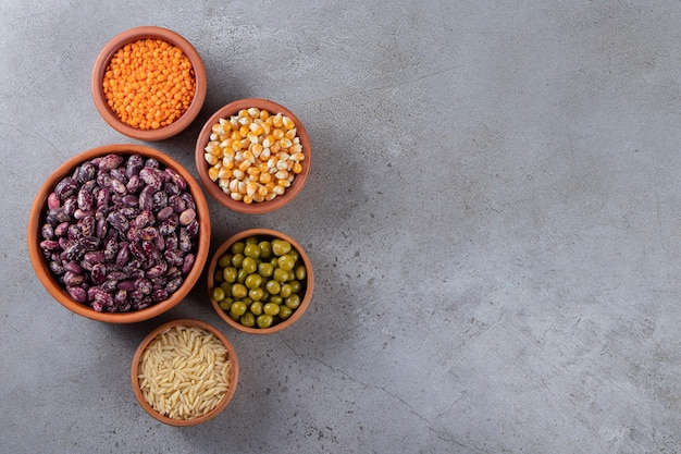 Clay bowls full of raw lentil, peas and beans on stone background.