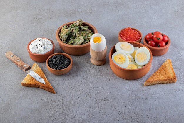 Глиняные миски здорового завтрака с яйцами и икрой на столе.