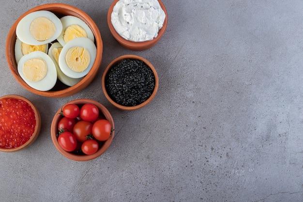 Глиняные миски здорового завтрака с яйцами, сливками и икрой на столе.