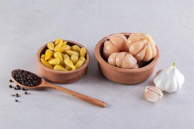 石のテーブルにニンニクと唐辛子のピクルスの粘土ボウル。