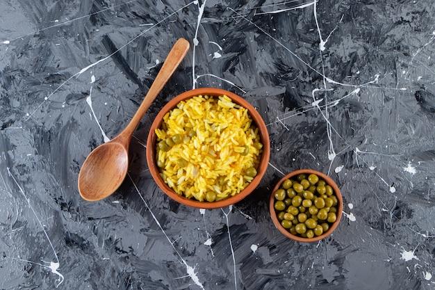 Глиняные миски с отварным рисом и зеленым горошком на мраморной поверхности.