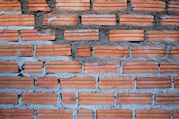 The clay brick wall was recently formed with cement.