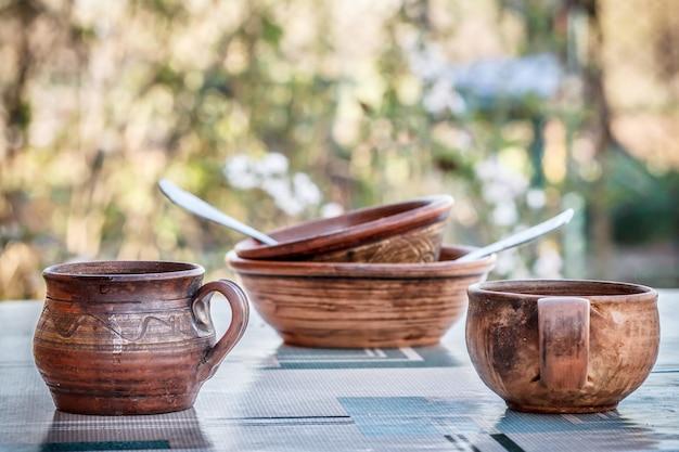 점토 컵 항아리와 숟가락이 있는 접시는 자연 흐릿한 배경으로 야외에 머물고 있습니다.
