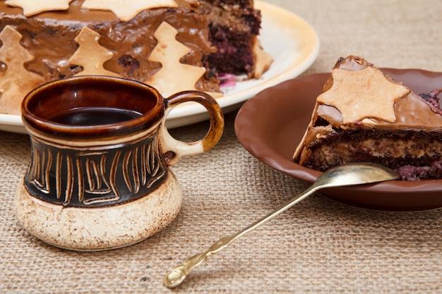 ブラックコーヒーの粘土カップ、荒布を着たテーブルの上のクリスマスの飾りで飾られた自家製チョコレートケーキ。