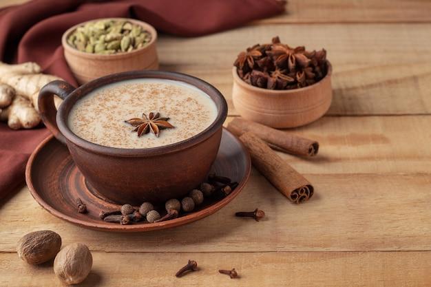 木製のテーブルにインドのマサラティーとスパイスと粘土カップ