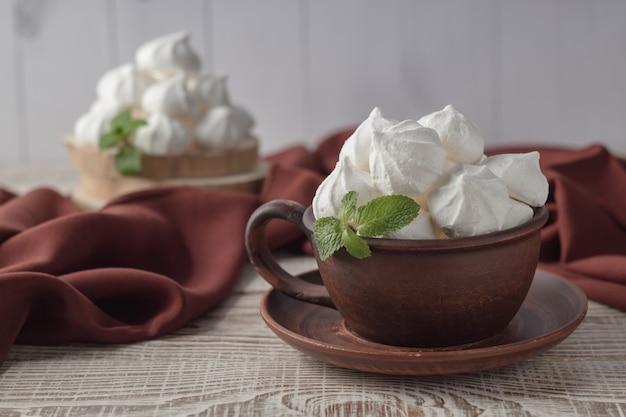 白い木製のテーブルにバニラメレンゲのキスと粘土のカップ