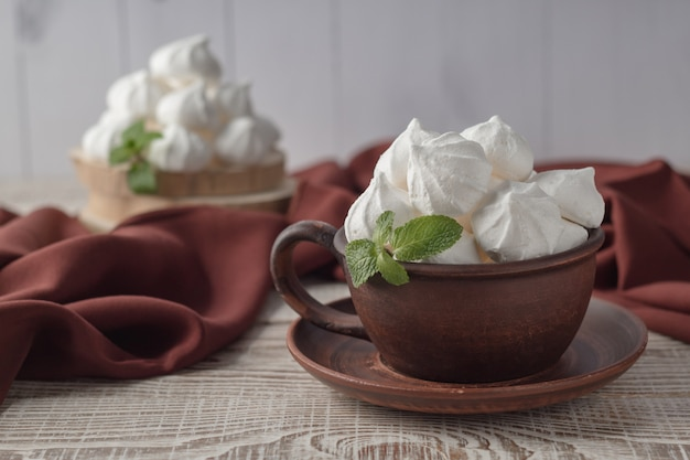Clay cup with vanilla meringue kisses on white wooden table