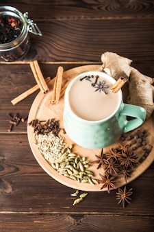 Clay cup on a wooden board on a dark background. a cup of masala tea. spices cloves, fennel, cinnamon, cardamom, milk.