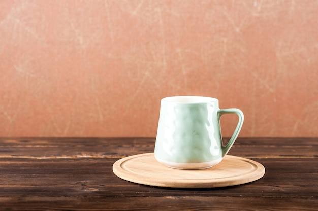 Clay cup on a wooden board on a dark background.
