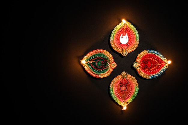 Clay diya lamps lit  during dipavali celebrate on black background