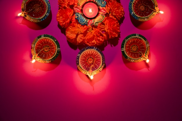 Clay diya lamps lit  during dipavali celebrate on pink background