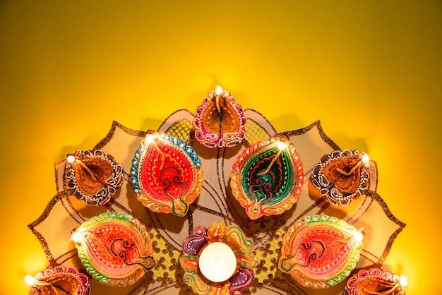 Clay diya lamps lit  during dipavali celebrate on yellow background