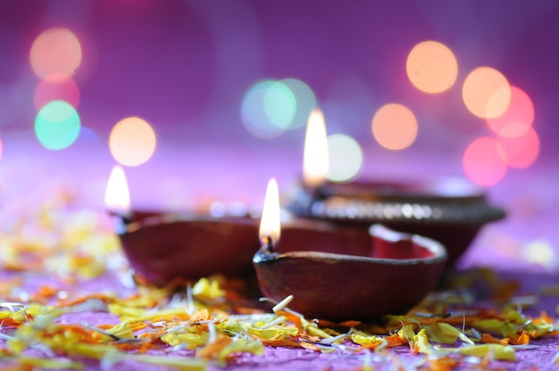 Clay diya lamps lit during diwali celebration. greetings card design indian hindu light festival called diwali
