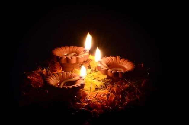 Clay diya lamps lit during diwali celebration. greetings card design indian hindu light festival called diwali