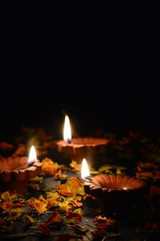 Clay diya lamps lit during diwali celebration. greetings card  indian hindu light festival called diwali