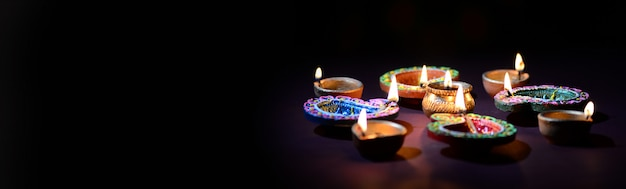 Clay diya lamps lit during diwali celebration. greetings card  indian hindu light festival called diwali