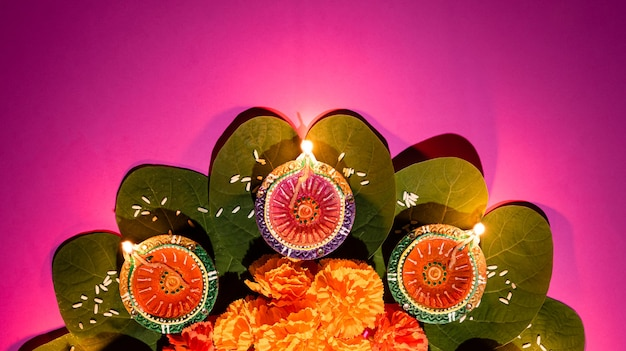 Clay diya lamps lit during dussehra with yellow flowers, green leaf and rice