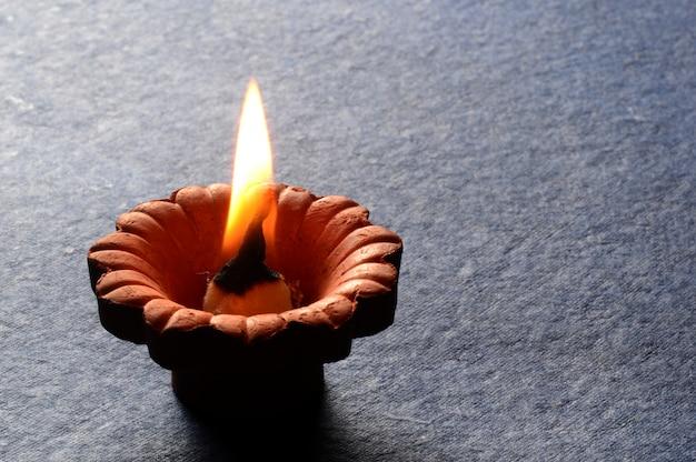 Лампы clay diya зажжены во время празднования индийского индуистского фестиваля света под названием дивали