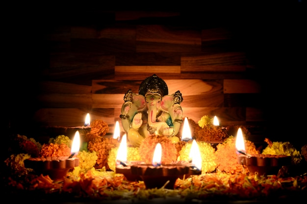 Clay diya lamps lit with lord ganesha during diwali celebration. greetings card design indian hindu light festival called diwali