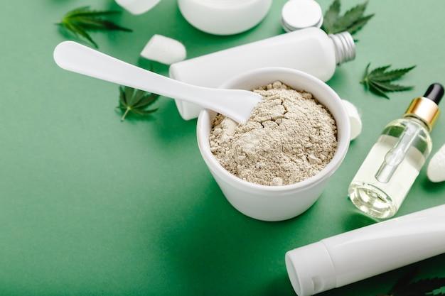 Cbd 대마초가 주입 된 클레이 페이스 마스크 및 녹색 표면에 스포이드 대마초 잎에 cbd 오일 세럼이있는 흰색 튜브에 스킨 케어 화장품을 설정하십시오.