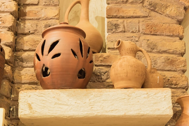 Clay jars on a stone shelf in orient room. close up