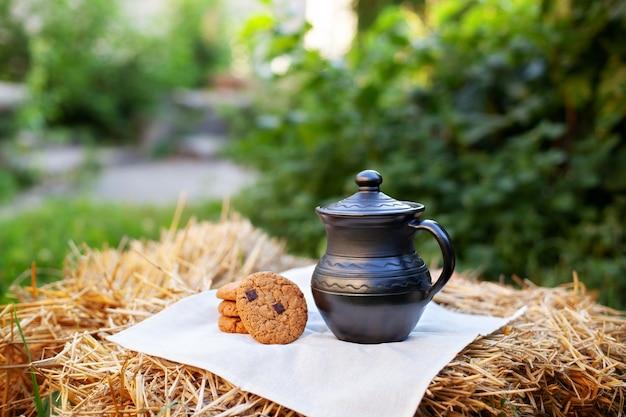 Глиняный кувшин, домашнее печенье на соломе в саду.