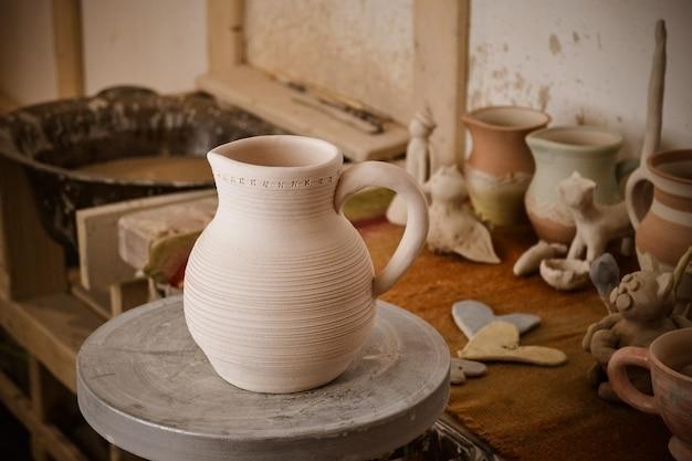 Clay jug on a potter's wheel close-up. copy spase