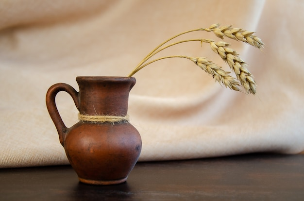 Clay jug with ears of wheat on wooden table against background of beige curtain. rustic still life