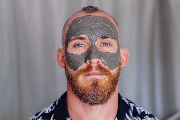 뷰티 클리닉에서 젊은 잘 생긴 남자의 얼굴에 클레이 마스크