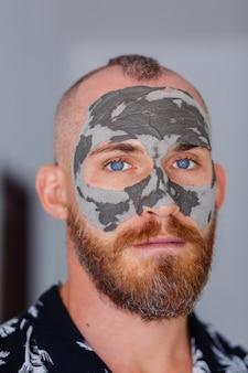 Maschera di argilla sul viso giovane uomo bello in clinica di bellezza