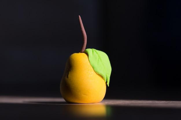 Clay miniature yellow pear on dark