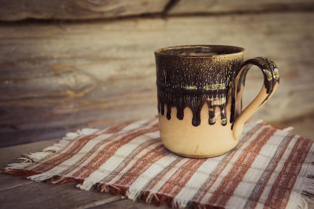 木製のベンチにタオルで粘土マグカップ