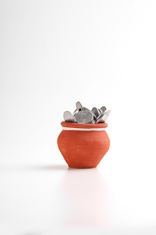 Clay piggy bank pot filled with indian rupees coin