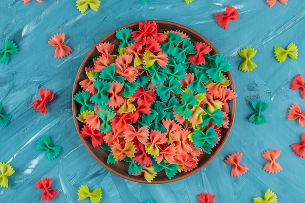 Clay plate of colorful raw farfalle pasta on blue surface