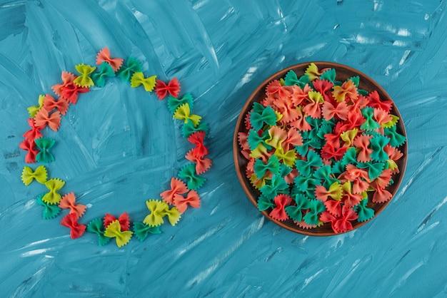 Piatto di argilla di pasta colorata farfalle crudo sulla superficie blu