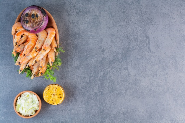 A clay plate of delicious shrimps with sliced lemon and onion on a stone surface