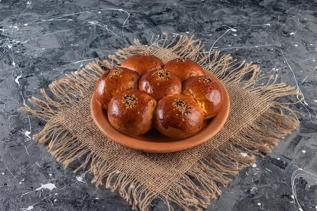 Piatto di argilla di pasticceria fresca con semi di sesamo sul tavolo di marmo.