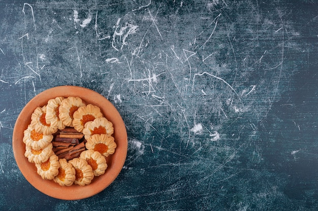 Piatto di argilla pieno di biscotti di gelatina e bastoncini di cannella su marmo.