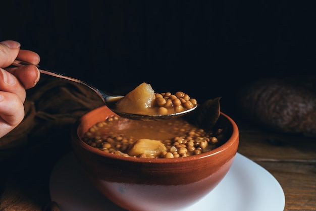 暗い木製の背景にジャガイモとグラスワインとレンズ豆の粘土プレート。暗い食べ物。