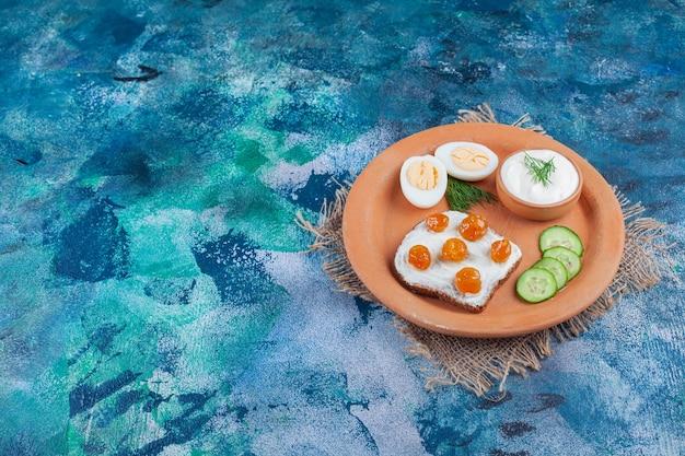 Piatto di argilla di pane a fette con crema bianca e marmellata di frutti di bosco su superficie blu.