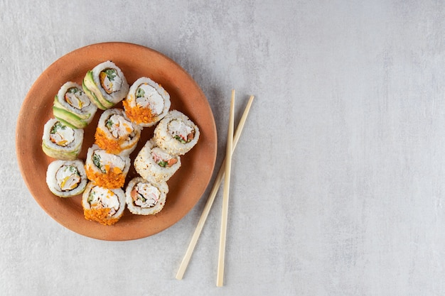 Clay plate of various sushi rolls placed on stone surface