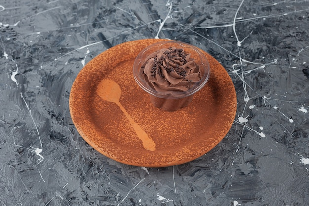 Clay plate with chocolate creamy cupcake on marble surface.